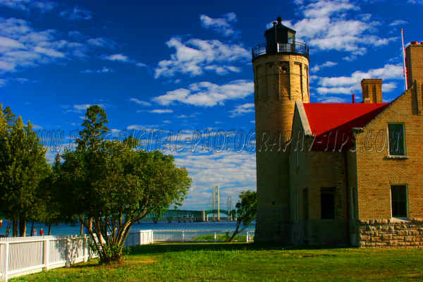 Mackinaw City lighthouse on a beautiful summer day with the Mackinaw bridge in the background, in the Upper Peninsula of Michigan.