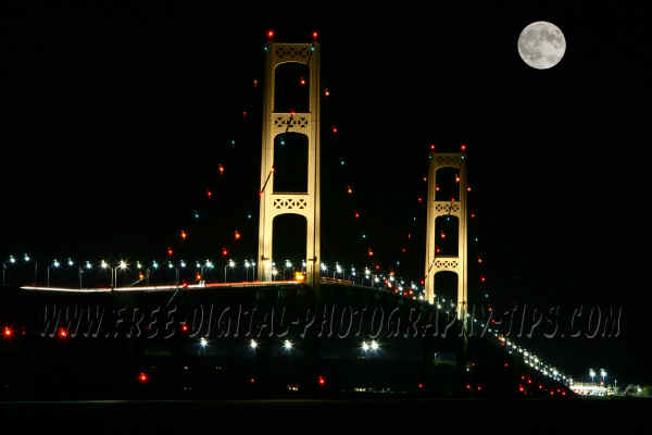 Mackinaw Bridge lit up at night with the moon in Upper Michigan.