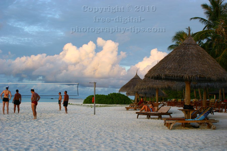 group tourists playing fun game beach volleyball soft white sandy beach Sun Island Maldives