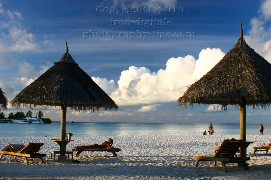 sun island maldives white sandy beach lounge chair sand hut fluffy clouds sunset turquoise ocean