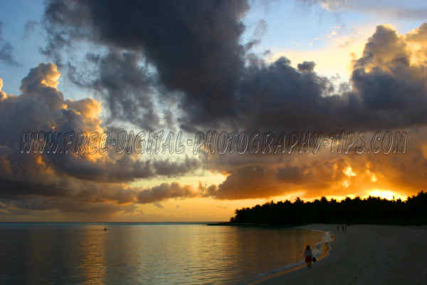 Another gorgeous Maldives sunset tourists having relaxing time walking white sandy beach Sun Island Maldives