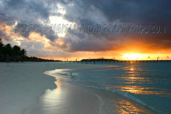 Still another magnificent Maldives sunset small gentle waves rolling white sandy beach Sun Island Maldives